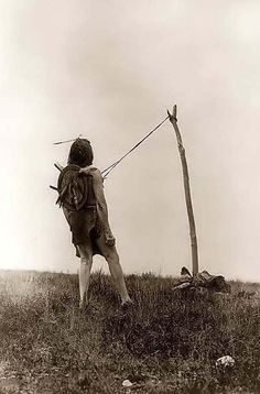 This is a rare photograph of the Native American Piercing Ritual, a rite of manhood among the Indians.  1908 by Edward S. Curtis the photograph illustrates a Crow man, leaning back slightly, with strips of leather attached to his chest by sticks pierced through his breast. He is tethered to a pole that is secured by rocks. This is all part of the piercing ritual of the sun dance.
