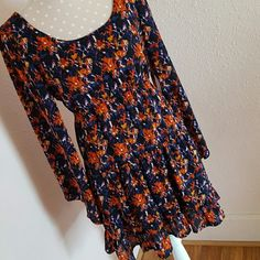 Boho cut-out dress Beautiful boho chic dress. Cut-out design in back of dress. Bell sleeves. Ruffled bottom. Elastic waist. Adorable with tall boots and boho jewelry! Orange, mustard, and navy splattered design. Love by Design Dresses Backless