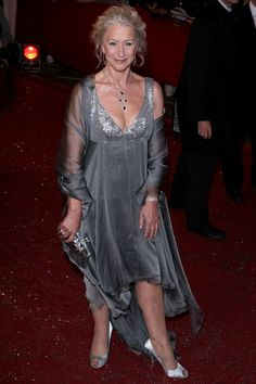 Helen Mirren Style Highs (2007) ~ Wearing a glamorous silver evening gown, teamed with matching shawl and diamond-encrusted jewels. Silver lame bodice, with deep V neckline; shoulder straps. The layered sheer silk skirt has a decending hemline, creating a floating effect. Matching scarf. Silver shoes and clutch