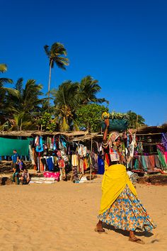 Woman in traditional Goan dress selling fruit in front of the souvenir stalls, beach huts and restaurants which line the beach in Anjuna, located in Northern Goa.
