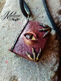 Dragon eye book, containing powerful spells. Handmade pendant, designed from top quality polymer clay. Easy to wear, and looks great while you're wearing it. Perfect as a gift for book or fantasy lovers. #MelianArt #HandmadeJewelry #DragonBook #DragonNecklace #Grimoire #SpellBookNecklace #WiccaJewelry #GothicJewelry #ProtectionNecklace #MagicBook