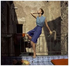 "Model Sherry ""Cherry"" Nelms resting on railing wearing blue knee-length culottes with brass buttons and sea-green high throated shirt. Circa January 1955, Palermo, Sicily Photo Henry Clarke"