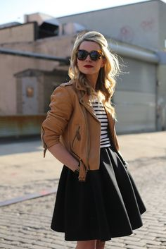 Tan moto jacket, black and white striped shirt, and black midi skirt