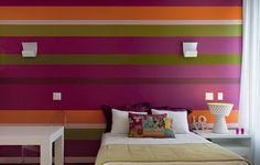 """O colorido é perfeito para quartos de adolescentes. A arquiteta Andrea Murao elegeu os tons de roxo, verde e laranja e criou listras, ora finas, ora grossas. Siga as dicas da profissional: """"O resultado fica melhor em uma parede sem janela"""""""