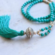Long Turquoise Beaded Tassel Necklace with Silver Tibetan Focal Bead. On trend tassel necklace with rich turquoise tassel. Turquoise is perfect to wear all year round. It looks great with black, denim, beige and white. I think it would look great with a camel poncho. We made it with 8mm