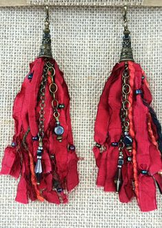 This earring is so rich and royal. You can't beat this red!! These tassel earrings are created with a beaded, red ribbon and soft, yarn pieces. Antiqued brass chains mix and mingle with the tassel and
