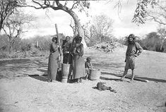 """Aloha sister """"Meg"""" in the books or Miki as I knew her, with Shangaan woman who grinding the grain with pestle and mortars by hand. Meg was the """"chef"""" on the Wanderwell Expeditions and is waiting for grain. Mozambique Shangaan Village in South Africa 1926-1927. . www.AlohaWanderwell.com"""