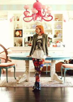 Hayley in her dining room with her pink octoupus- like chandelier
