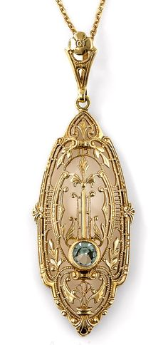 Art Deco Aquamarine Pendant Necklace. A single pale blue aquamarine gleams from within this striking and unusual Art Deco pendant necklace, die-struck and hand finished in rich 14K yellow gold - circa 1930s. Fanciful foliate and geometric filigree coalesce for an enchanting neoclassical effect. 1 and 7/8 inch from the top of the loop, the chain measures 18 inches.