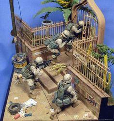 Magnífica viñeta/diorama ambientada en Irak de un grupo de soldados peinando una calle casa por casa en busca de terroristas o insurgentes.