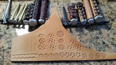 Create your own Leather Tooling Stamps by Lake Havasu Leather.  Take a Large Bolt, Door Hinge Pin, even a large Nail.  Use a Dremel tool with a small sanding stone to create a pattern.  Remember you are making the negative ,  so whatever pattern you want needs to be reversed.