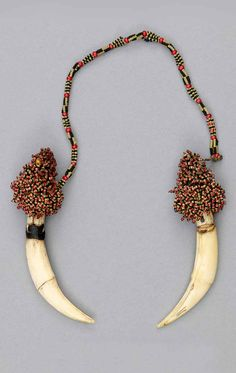 Malaysia - Sarawak | Ear ornaments from the Kayan people | Tiger claw, glass beads and fiber.  ca. 1927 or earlier  | © UBC Museum of Anthropology. No. B36