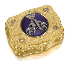 An Imperial Presentation jeweled gold and enamel box, Charles Collins & Söhne, Hanau, 1849-1855. Of cartouche form, the lid centred with a translucent Royal blue enamel roundel applied with the diamond-set crowned cypher of Grand Duke Alexander Nikolaevich, later Emperor Alexander II, within raised and engraved foliated fretwork and applied rosettes, in a plush-lined box for Friedrich Butz, St Petersburg.