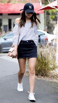 Look com mini saia jeans com blusa ombro a ombro listrada e boné.