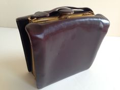 Elegant handbag, brown leather, made by EVANS. Claps in metal work an example of American Modern Streamline, with gold accents. Box style design comes with ladies accessories, including a mirror, change purse, compact, and lighter. Lovely piece that is gently used but in wonderful shape for its age. Large enough to hold modern accessories such as Iphone, wallet, keys and more. Two compartments with four (4) pockets. Snap shut closure. Measures 8.5 x 8 4, leather on one side marked  Great…