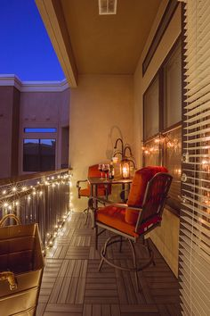 A small balcony light up at night by string lights and candles
