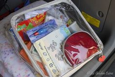 """Busy Bags: stocked with crayons, a coloring book, stickers, blank paper, a set of Aquadoodle pages with the """"magic"""" water coloring pens, a Thomas the Train take-along play set, dry erase board and markers, and various tiny toys (a Hot Wheels car, a Star Wars figure, and a toy airplane)."""