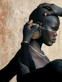 Surma man helping a young woman with her face painting, Africa.