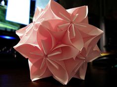 Origami flowers hooked together to make flower balls. They used post it notes here--