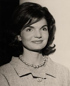 A beautiful black and white photo of jackie wearing her one strand of pearls and is kind of smiling for the camera.