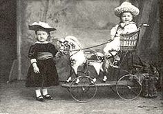 Shows a black and white photograph of two small girls in front of a painted landscape backdrop. One is sitting on a chair mounted on a hobby horse on wheels.
