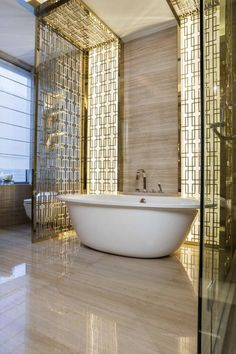 In this bathroom design, Kelly Hoppen decided to add a touch of glamour and improve the luxury interior design of the space with a gold screen with art deco inspiration.