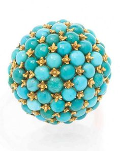 An 18 Karat Yellow Gold and Turquoise Bombe Ring, Italian, containing numerous round cabochon cut turquoise secured with yellow gold claw settings, the gallery finished with intricate open scrollwork. Stamp: 750