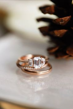 Sleek and chic! This beauty's sparkle is unreal! Here we have our three stone Varsha emerald cut engagement ring paired with the Roxanna and Daylight bands. Shown here in 14k rose gold.