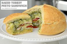 Baked Turkey Pesto Sandwich  Author:Aimee Lane  1 Loaf Sourdough Bread, cut top and hollow out  ½ pound Turkey Deli Meat  ¼ cup Pesto Sauce  1 Tomato Sliced  1 Small Zucchini, sliced thinly  8 Slices, Mozzarella Cheese  Instructions  Layer ½ of ingredients and then repeat.  Cover open sandwich with bread lid.  Wrap in aluminum foil.  Bake for 35-45 minutes.  Cut into wedges and serve warm.