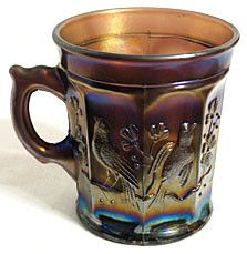 This is a beautiful amethyst carnival glass mug in the Singing Birds pattern that was made by Northwood. It stands 3.5 inches tall and is marked in the bottom with the N in a circle Northwood mark. Th