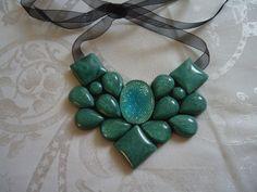 Maxi colar em tons verde. chatons de gotas, quadrados e botões verde imitando marmore, 1 chaton central oval verde com brilho. Fecho em fita de organza preta. R$34,90