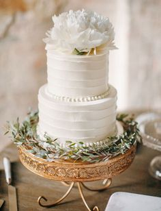 white wedding cake on a gold cake stand
