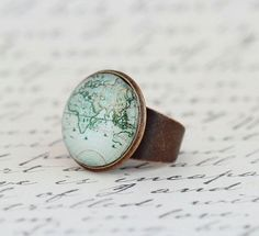 World Map Statement Ring    This brass statement ring has a wide adjustable ban and boasts a copy of a vintage map print below a glass dome.