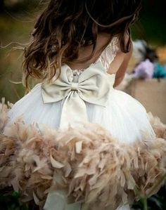 This is the cutest flower girl dress I have ever seen! Those feathers are gorgeous, and it's just the right ballence of little girl and serious occasion!
