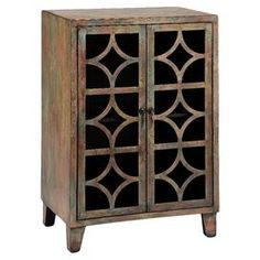 """Bring rustic-chic appeal to your living room or den with this 2-door cabinet, showcasing latticed overlay facings and a distressed finish.     Product: CabinetConstruction Material: Engineered woodColor: Cafe au laitFeatures:  Hand-paintedTwo doorsInterior shelving Dimensions: 35.5"""" H x 23.5"""" W x 15.75"""" D"""