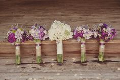 The bridesmaids will carry clutch bouquets of lavender stock flowers, fresh lavender, lavender spray roses, Queen Anne's lace, and dark purple sweet peas, and small tufts of pink astilbe wrapped in gray ribbon with the stems showing.