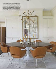 "Dining room in the Connecticut home of Design With Reach president/CEO John Edelman and photographer Bonnie Edelman: Eero Saarinen Oval Dining Table and Executive Armchairs upholstered in a cognac leather with a Satellite chandelier overhead | House Beautiful April 2012 ""The Warm Side of Modern"""