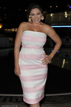 Flattering her figure: The pink and white striped dress clung on tightly to her ample bust before cinching in her tiny waist