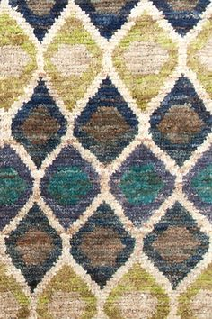 Test drive this rug in your space.Order a swatch by adding it to your cart.Pretty as a peacock! This eco-friendly jute area rug, colored with vegetable dyes, features a repeating pattern of irregular diamonds in teal, navy, grey, amber, and ivory.