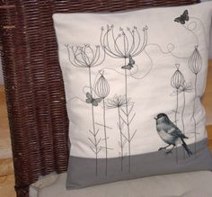 Embroidered and appliqued covered cushion with bird and butterflies.