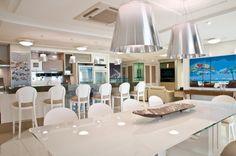 A mesa de jantar traz tampo de vidro clear pintado de branco e acomodações para dez pessoas.