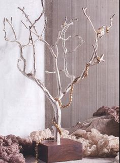 centerpiece idea. stain wodden block color you would want. drill a hole through the block and the branch to hold in place. spray paint branches black