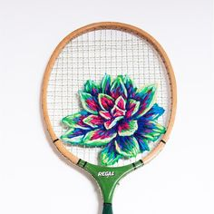 Chicken wire, coffee bags, vintage athletic rackets, a United Nations fence: just some of the surfaces Danielle Clough (@fiance_knowles) vividly embroiders with nature motifs. Here's a desert rose succulent, rendered on an old tennis racket. Photo by @sarahnankin.