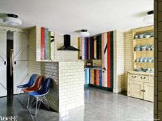 The owners of this London kitchen sourced the wall's ceramic tiles from the London tube's tilemaker. The colourful units were made from reclaimed floorboards from a squat. To the left is a line-up of vintage Eames 'DSR fiberglass' chairs.    From 'The Right Track', a story on page 110 of Vogue Living Jan/Feb 2010.    Photograph by Richard Powers.