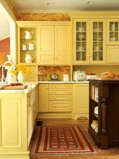 Butter-yellow cabinetry is the star of this kitchen, but dollops of red-figured pastoral toile wallpaper bring country character to the space. The charming pattern prevents the cabinetry from overwhelming the eye and adds depth to the backsplash and cornice. Pattern in the Kitchen