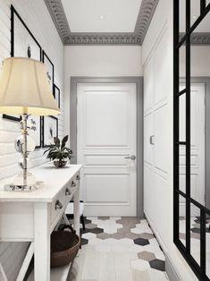 deco couloir en noir, blanc gris et taupe, grand miroir avec cadre noir et éléments décoratifs en noir, meuble d'entrée, table blanche en style shabby chic, lampadaire avec abat jour beige au design classique, tableaux en noir et blanc avec des cadres noirs, plafond blanc avec cadre en frises grises