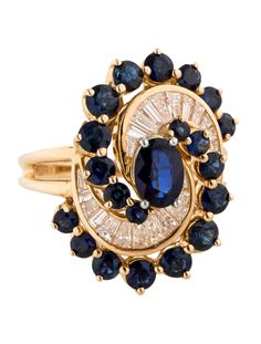 18K yellow gold Oscar Heyman ring with platinum set blue sapphire at center and blue sapphire and diamond swirl motif. Ring size 6. This item has been appraised and inspected by our certified gemologist. All gemstone weights and measurements are approximate.