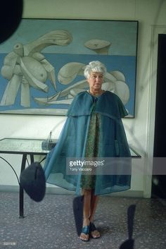 Full-length image of American art collector <a gi-track='captionPersonalityLinkClicked' href='/galleries/personality/228041' ng-click='$event.stopPropagation()'>Peggy Guggenheim</a> (1898 - 1979) standing in front of a Picasso painting 'On The Beach' at the <a gi-track='captionPersonalityLinkClicked' href='/galleries/personality/228041' ng-click='$event.stopPropagation()'>Peggy Guggenheim</a> museum, Venice, Italy. She wears a light blue cape and a floral dress.