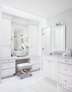 11. Plentiful Storage Space  This master bathroom was reimagined in white-on-white with Wood-Mode's Brookhaven cabinetry, which offers plenty of storage space. The ottoman from 1stdibs and sconces by Visual Comfort add yesteryear charm. Fixtures and faucets are by Rohl.