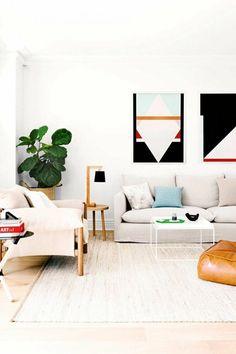 salon scandinave avec des tableaux d'art modernes